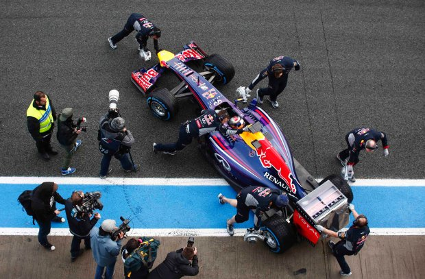 Red Bull Formula One driver Sebastian Vettel of Germany sits inside his RB10 as team members push his car into the garage during pre-season testing at the Jerez racetrack in southern Spain January 29, 2014. Formula One may have to 'revisit' a controversial rule change awarding double points for the final race of the season because of the backlash from fans, according to Mercedes motorsport head Toto Wolff.  REUTERS/Marcelo del Pozo (SPAIN - Tags: SPORT MOTORSPORT)