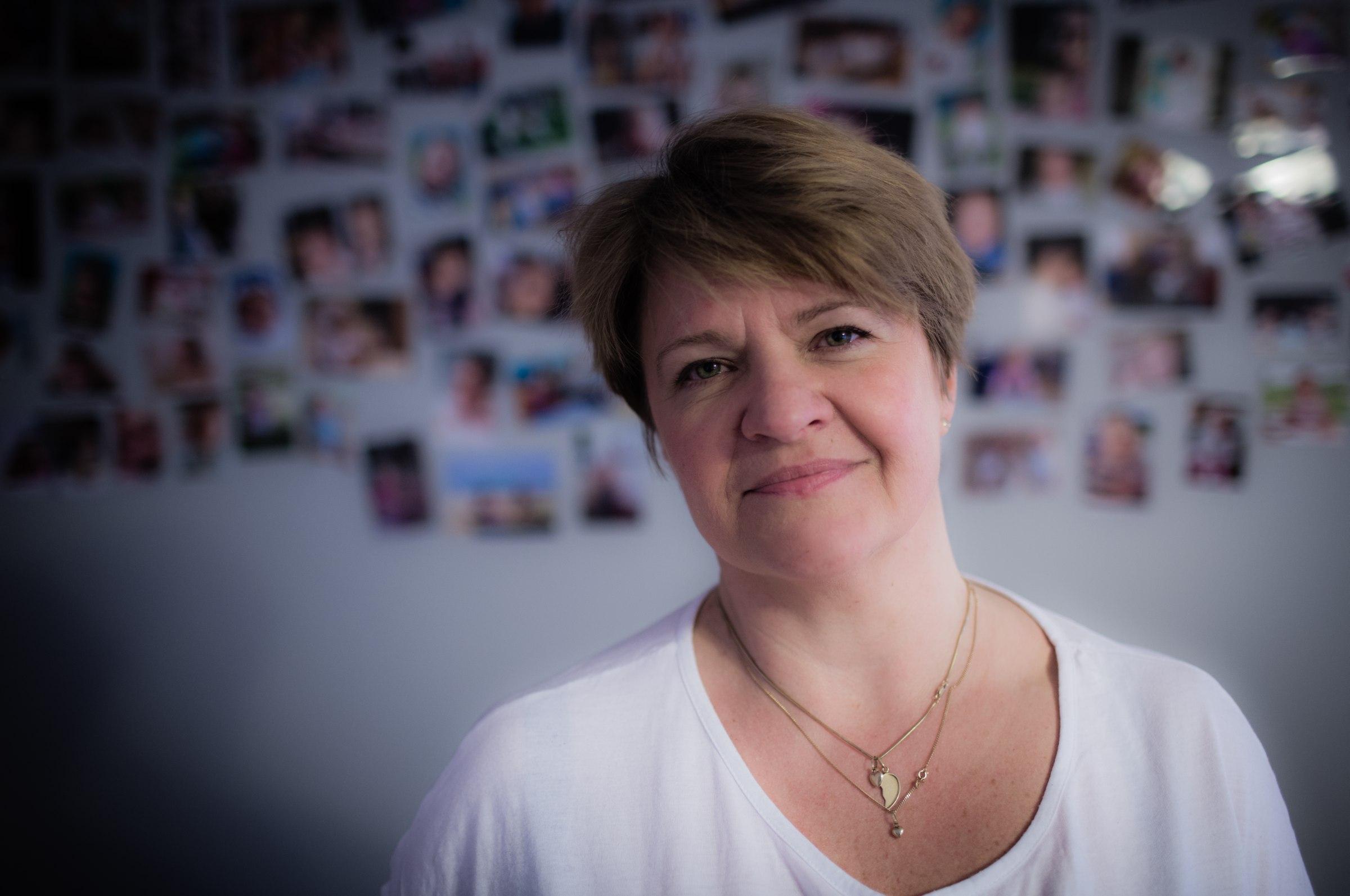 Katarzyna Kowalska. W tle ściana ze zdjęciami dzieci, którymi się opiekowała (fot. Albert Zawada / Agencja Gazeta)