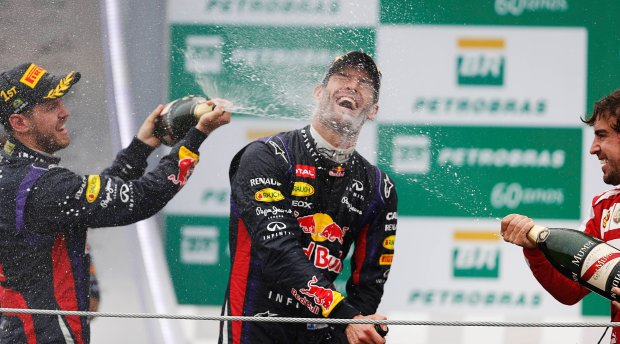 Red Bull Formula One driver Sebastian Vettel (L-R) of Germany, teammate Mark Webber of Australia and Ferrari Formula One driver Fernando Alonso of Spain spray champagne as they celebrate on the podium after the Brazilian F1 Grand Prix at the Interlagos circuit in Sao Paulo November 24, 2013.   REUTERS/Nacho Doce (BRAZIL  - Tags: SPORT MOTORSPORT F1)