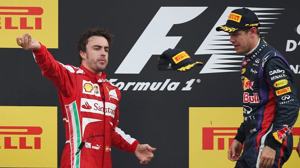 Ferrari driver Fernando Alonso of Spain, left, second place, tosses his cap to supporters as winner Red Bull driver Sebastian Vettel of Germany watches, on the podium after the Italian Grand Prix, at the Monza Formula One circuit, in Monza, Italy, Sunday, Sept. 8, 2013. (AP Photo/Luca Bruno)