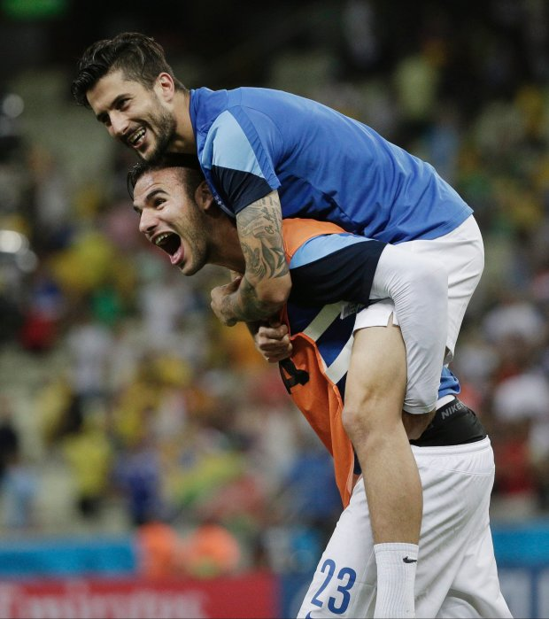 Greece's Panagiotis Tachtsidis carries his teammate Panagiotis Kone after their 2-1 victory over Ivory Coast during the group C World Cup soccer match between Greece and Ivory Coast at the Arena Castelao in Fortaleza, Brazil, Tuesday, June 24, 2014. (AP Photo/Bernat Armangue)