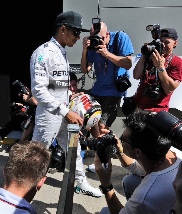 Mercedes driver Lewis Hamilton of Britain walks past photographer during the driver portrait session in the paddock ahead of the Australian Formula One Grand Prix at Albert Park in Melbourne, Australia, Thursday, March 13, 2014. (AP Photo/Rob Griffith)