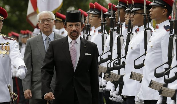 Brunei Sultan Hassanal Bolkiah, center, accompanied by Singapores President Tony Tan, center left, inspects a guard of honor guard during a welcome ceremony, Monday, April 21, 2014 at the Istana or Presidential Palace in Singapore. (AP Photo/Wong Maye-E)