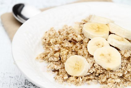 Oatmeal with fresh bananas drizzled with honey over a rustic wooden background.