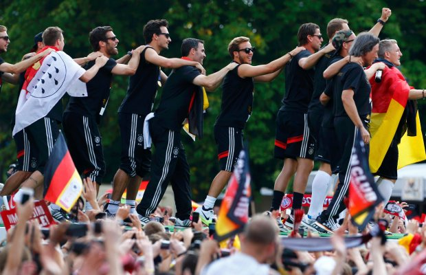 Members of Germany's 2014 Brazil World Cup squad appear on stage during celebrations to mark the team's 2014 Brazil World Cup victory, at a 'fan mile' public viewing zone in Berlin July 15, 2014.  Germany's victorious soccer team led by coach Joachim Loew returned home on Tuesday after winning the 2014 Brazil World Cup. A triumphant Germany team landed in Berlin on Tuesday to a hero's welcome, greeted by hundreds of thousands of jubilant Germans waving flags and wearing the national colours, revelling in the nation's fourth World Cup victory on Sunday in Brazil.                      REUTERS/Thomas Peter (GERMANY  - Tags: SPORT SOCCER WORLD CUP TPX IMAGES OF THE DAY)