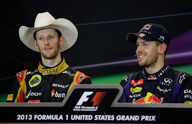 Lotus driver Romain Grosjean, left, of Switzerland wears a cowboy hat during a press conference with Red Bull driver Sebastian Vettel of Germany following the Formula One U.S. Grand Prix auto race at the Circuit of the Americas, Sunday, Nov. 17, 2013, in Austin, Texas. Vettel was first and Grosjean finished second. (AP Photo/Darron Cummings)