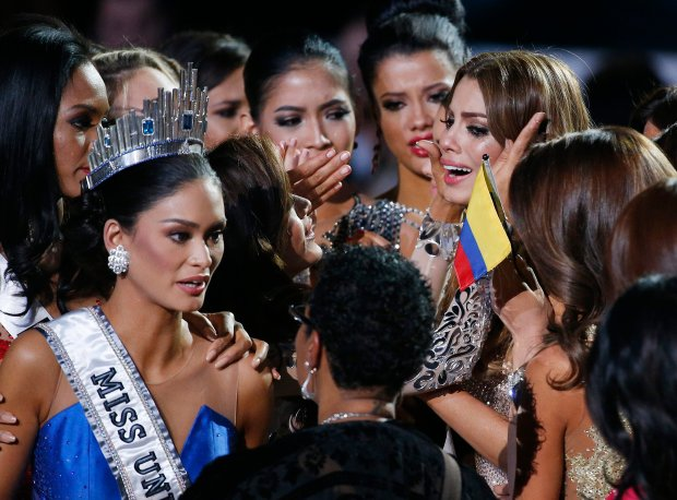 Other contestants comfort Miss Colombia Ariadna Gutierrez, top right, after she was incorrectly crowned Miss Universe at the Miss Universe pageant Sunday, Dec. 20, 2015, in Las Vegas. According to the pageant, a misreading led the announcer to read Miss Colombia Ariadna Gutierrez as the winner before they took it away and gave it to Miss Philippines Pia Alonzo Wurtzbach, pictured on left. (AP Photo/John Locher)