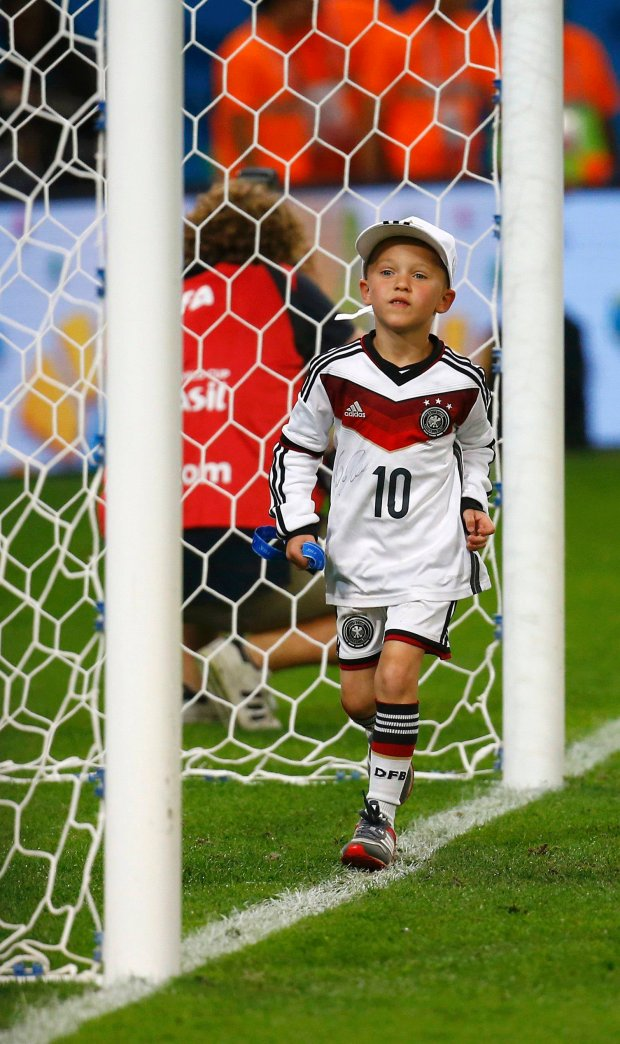 Louis Gabriel Podolski, son of Germany's Lukas Podolski, walks on the pitch with a medal after the team won their 2014 World Cup final against Argentina at the Maracana stadium in Rio de Janeiro July 13, 2014. REUTERS/Kai Pfaffenbach (BRAZIL  - Tags: SOCCER SPORT WORLD CUP)