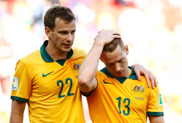 Australia's Alex Wilkinson comforts teammate Oliver Bozanic (R) after being defeated in their 2014 World Cup Group B soccer match against the Netherlands at the Beira Rio stadium in Porto Alegre June 18, 2014. REUTERS/Stefano Rellandini (BRAZIL  - Tags: SOCCER SPORT WORLD CUP)