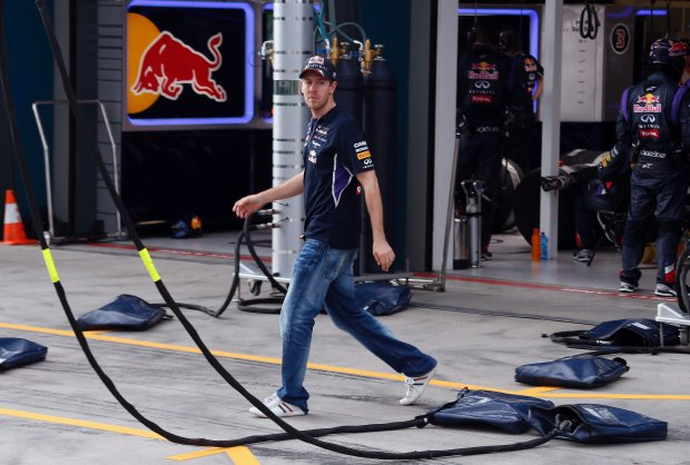 Red Bull driver Sebastian Vettel of Germany walks out of his team garage after retiring from the race in the Australian Formula One Grand Prix at the Albert Park in Melbourne, Australia, Sunday, March 16, 2014. Mercedes driver Nico Rosberg of Germany won the race ahead of Red Bull driver Daniel Ricciardo of Australia and McLaren driver Kevin Magnussen of Denmark. (AP Photo/David Gray, Pool)
