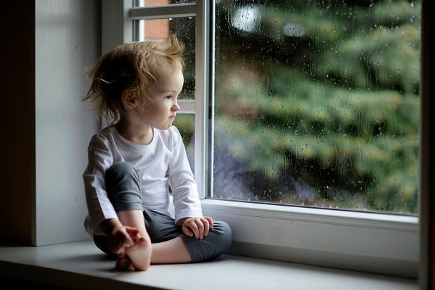 8Adorable toddler girl looking at raindrops on the window