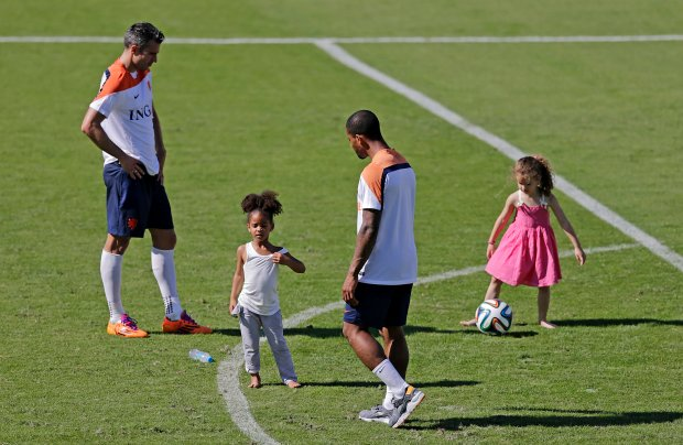 Robin van Persie, left, and Jeremain Lens of the Netherlands play with his daughters, after a training session in Rio de Janeiro, Brazil, Tuesday, June 24, 2014. Netherlands will play Group A runner-up Mexico in the second round on Sunday in Fortaleza. (AP Photo/Wong Maye-E)