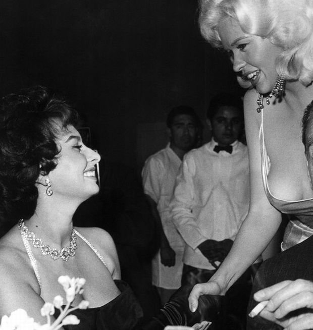 [Sophia Loren and Jayne Mansfield shake hands while Clifton Webb sits awkwardly by, ca. 1957